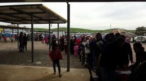 Refugees waiting in line for clothes at the distribution